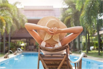 Woman Relaxing in front of a swimming pool